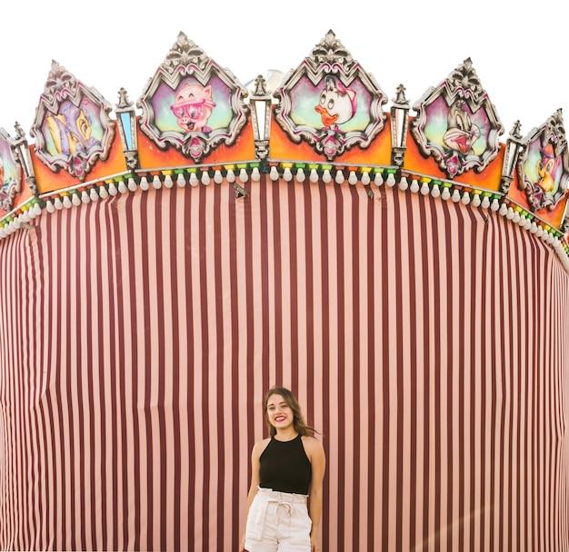 Jeune femme debout devant la tente au parc d'attractions