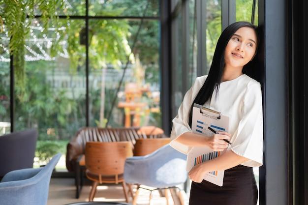 Jeune femme debout avec un document près de la fenêtre du bureau, concept d'entreprise