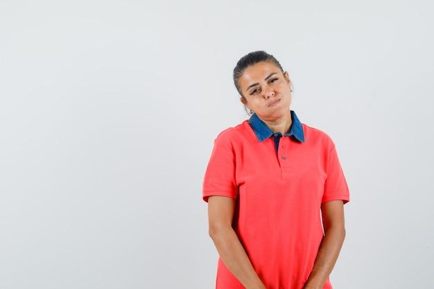 Jeune femme debout droite, joues gonflées et posant à la caméra en t-shirt rouge et à la jolie vue de face.