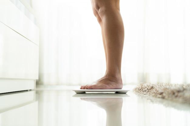 Jeune femme debout sur une échelle de poids numérique