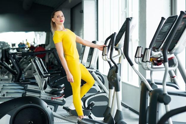 Jeune, femme, debout, elliptique, machine, gymnase