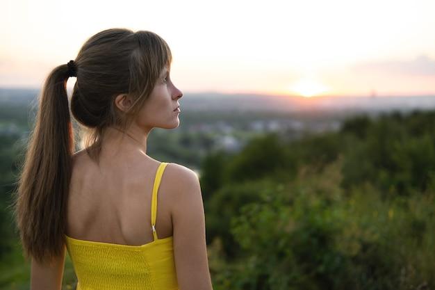 Jeune femme debout à l'extérieur, profitant de la vue sur le coucher du soleil