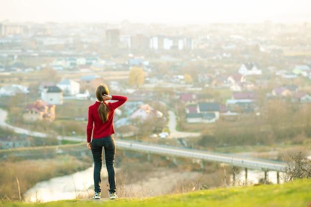 Jeune femme debout à l'extérieur, profitant de la vue sur la ville. concept de détente, de liberté et de bien-être.
