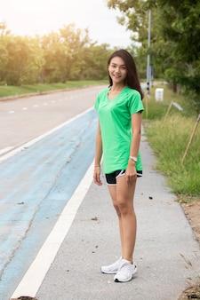 Jeune femme debout à l'extérieur en regardant la caméra et souriant