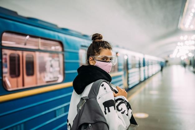 Jeune femme debout à la gare dans un masque de protection médical
