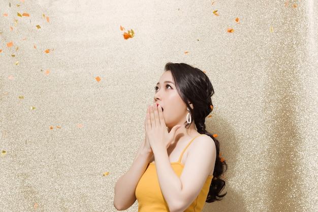 Jeune femme debout à l'intérieur sous des confettis colorés