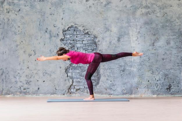 Jeune femme, debout, jambe, faire, fitness, contre, mur gris