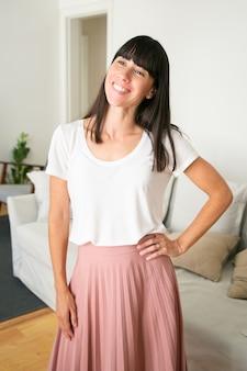 Jeune femme debout avec la main sur la hanche, souriant et regardant ailleurs.