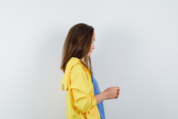 Jeune femme debout avec les mains jointes en t-shirt, veste et à la pensive.