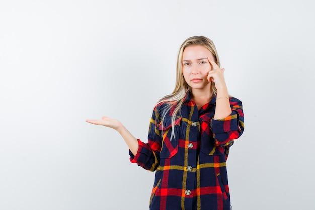 Jeune femme debout en pensant poser tout en montrant quelque chose en chemise à carreaux et à la vue de face, hésitante.