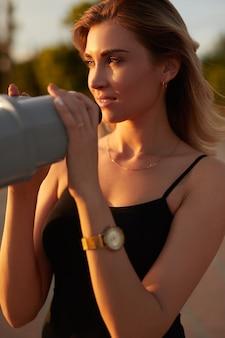 Jeune femme debout sur le point de vue avec des jumelles au soleil