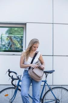 Jeune femme debout près de la bicyclette en regardant son sac à dos