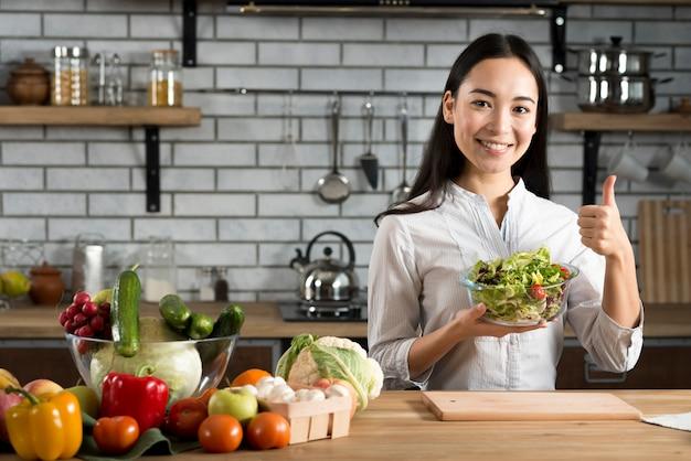 Jeune femme, debout, près, cuisine, compteur, projection, pouce haut, signe, tenue, salade légumes
