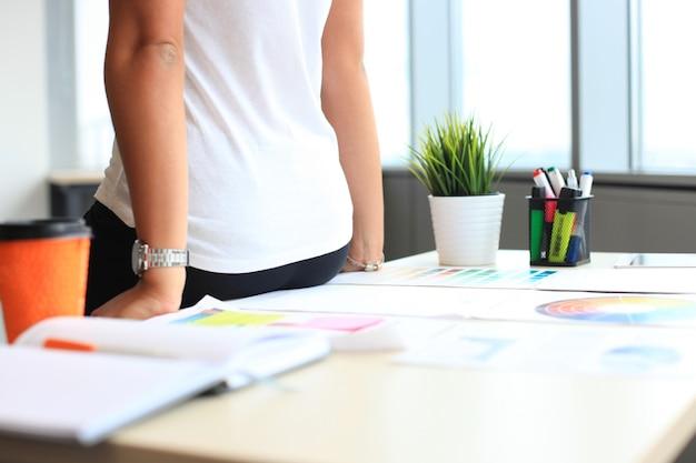 Jeune femme debout près du bureau avec instruments, plan et ordinateur portable