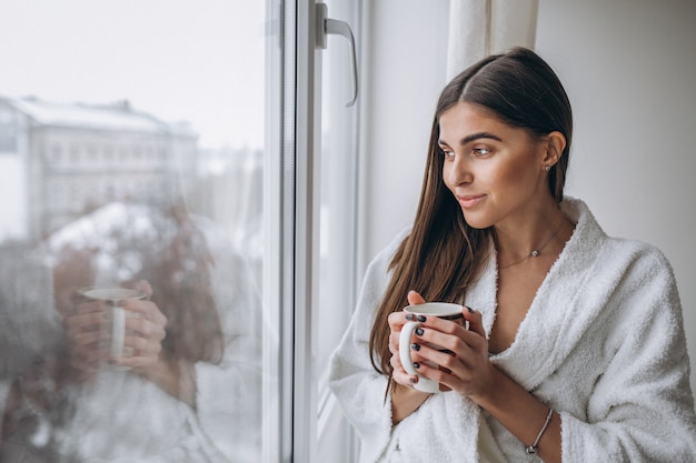 Jeune femme debout près de la fenêtre en buvant du café chaud