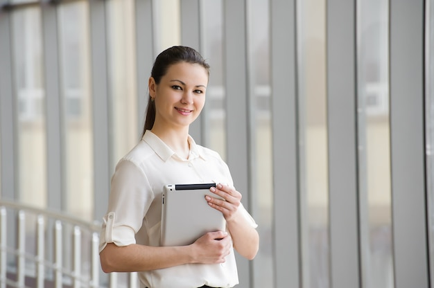 Jeune femme debout près de la fenêtre avec tablette.
