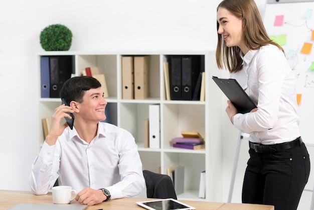 Jeune femme debout près de l'homme d'affaires souriant parlant sur téléphone mobile