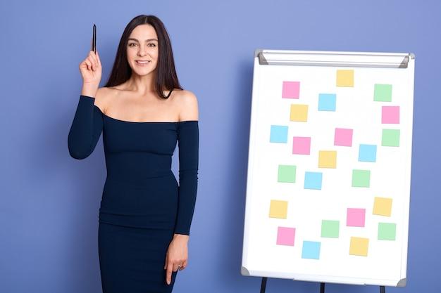 Jeune femme debout près de pense-bêtes sur le tableau de conférence, tenant un stylo en levant la main, ayant une grande idée d'entreprise, posant en robe isolée sur fond bleu.