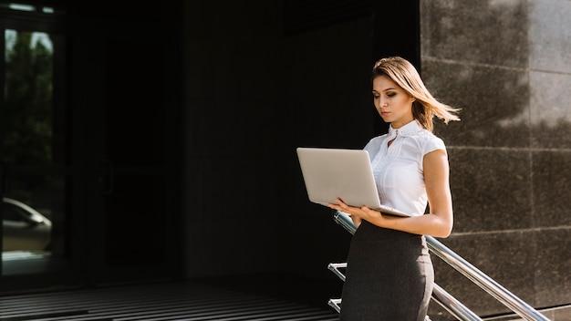 Jeune femme debout près de la rambarde regardant un ordinateur portable