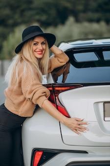 Jeune femme debout près de sa voiture blanche