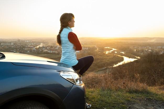Jeune femme debout près de sa voiture, profitant d'une vue chaude sur le coucher de soleil.