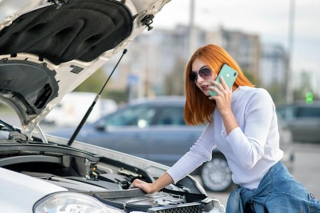 Jeune femme debout près d'une voiture cassée avec capot sauté parlant sur son téléphone portable en attendant de l'aide.