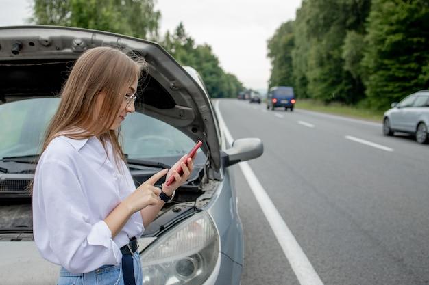 Jeune femme debout près de voiture en panne