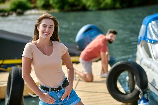 Une jeune femme debout sur le quai pendant que son homme détachait le bateau