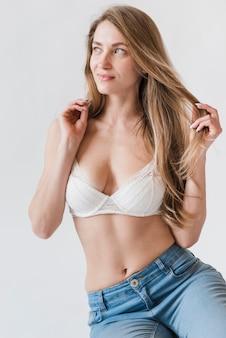 Jeune femme debout en soutien-gorge et jeans