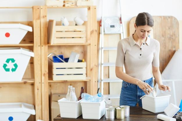 Jeune femme debout à la table et le recyclage des déchets dans les petites boîtes en entrepôt