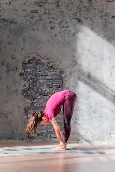 Jeune femme debout sur un tapis d'exercice faisant des exercices d'étirement