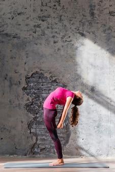 Jeune femme debout sur un tapis d'exercice se pliant en arrière contre un vieux mur