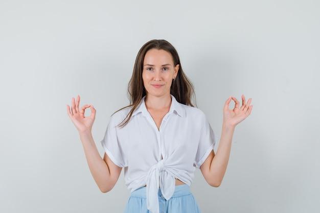 Jeune femme debout tout droit, montrant signe ok avec les deux mains en chemisier blanc et jupe bleu clair et à la confiance