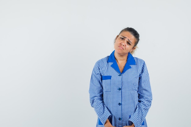 Jeune femme debout tout droit et posant à la caméra en chemise de pyjama vichy bleu et à la lugubre. vue de face.