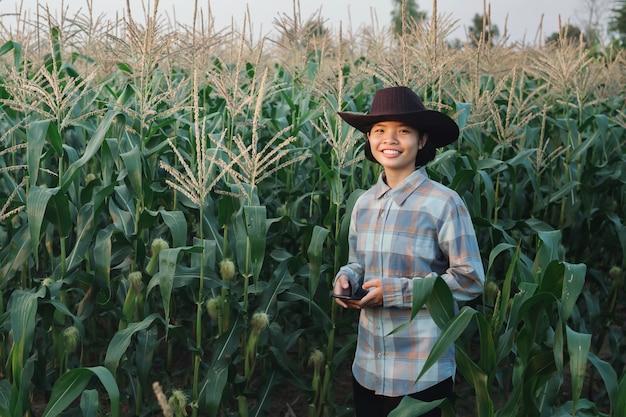 Jeune femme debout utilise mobile contrôle maïs dans ferme. technologie agriculture conept