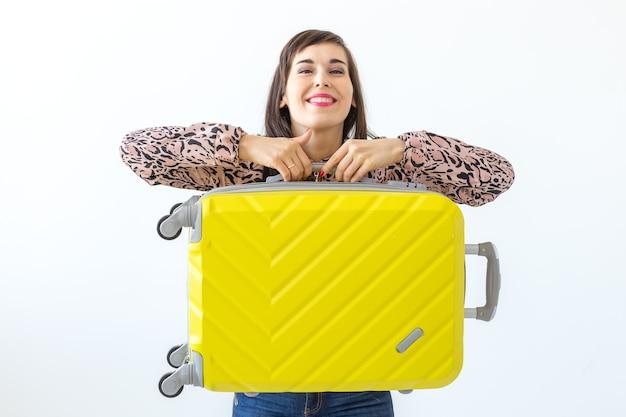 Jeune femme debout avec une valise jaune contre le mur d'un mur blanc avec espace copie
