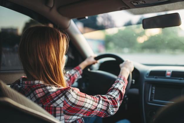 Jeune femme débutant au volant d'une voiture, vue arrière