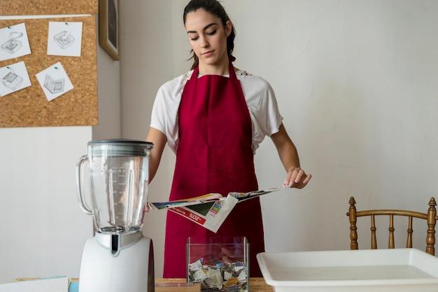 Jeune femme déchire le papier dans l'atelier
