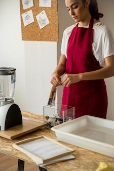 Jeune femme déchire le papier sur le récipient en verre