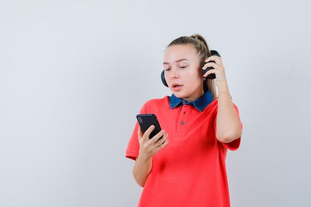 Jeune Femme, Décoller, écouteurs, Utilisation, Téléphone Portable, Dans, T-shirt Photo gratuit