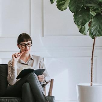Jeune femme décontractée assise sur un canapé avec son agenda