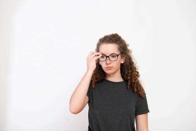 Jeune femme décontractée avec une coiffure frisée brune et des lunettes sur fond blanc