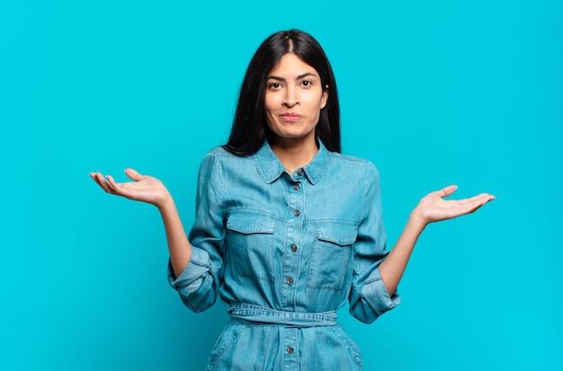 Jeune femme décontractée hispanique se sentant perplexe et confuse, doutant, pondérant ou choisissant différentes options avec une expression amusante