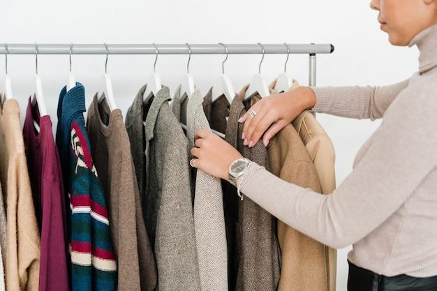 Jeune femme décontractée à la recherche d'une nouvelle collection saisonnière de vêtements en se tenant debout par rack en boutique