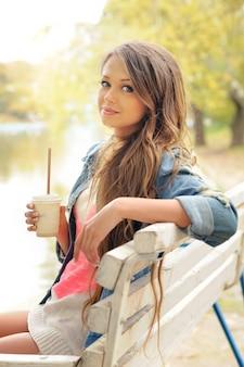 Jeune femme décontractée avec une tasse de café en papier relaxant en plein air dans le parc.