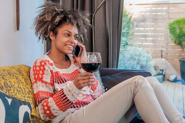 Une jeune femme décontractée utilisant un téléphone portable assis sur son divan chez soi et jouit d'un verre de vin. africaine, américain, femme, conversation, téléphone portable
