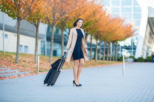 Jeune femme décontractée va à l'aéroport à la fenêtre avec une valise en attente d'avion