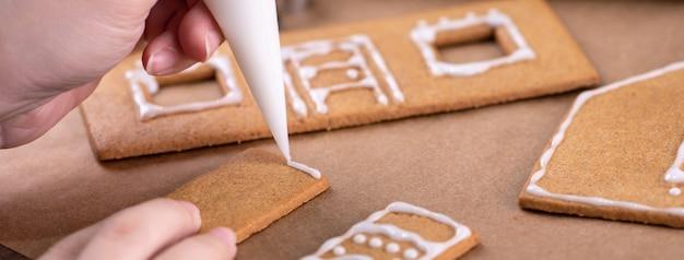 La jeune femme décore des biscuits de pain d'épice de noël