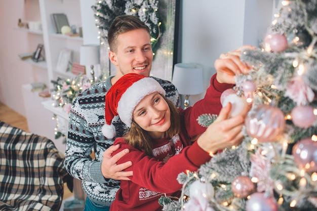Jeune femme décorer le sapin de noël. elle y touche un jouet. le jeune homme se tient derrière et l'embrasse. ils sourient.