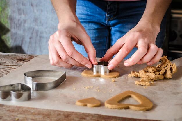 Une jeune femme découpe des figurines dans une pâte avec des bûches sur une table en bois